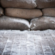 Old brown sandbags on snow covered wooden floor — Stock Photo #8196581