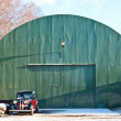 Old green aircraft hanger with classic car park in front — Stock Photo #8196606