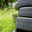 Old road tires stacked on grass land — Stock Photo #8198591
