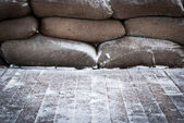 Old brown sandbags on snow covered wooden floor — Stock Photo
