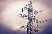 High power electrical pole on a cloudy day with silhouette — Stock fotografie