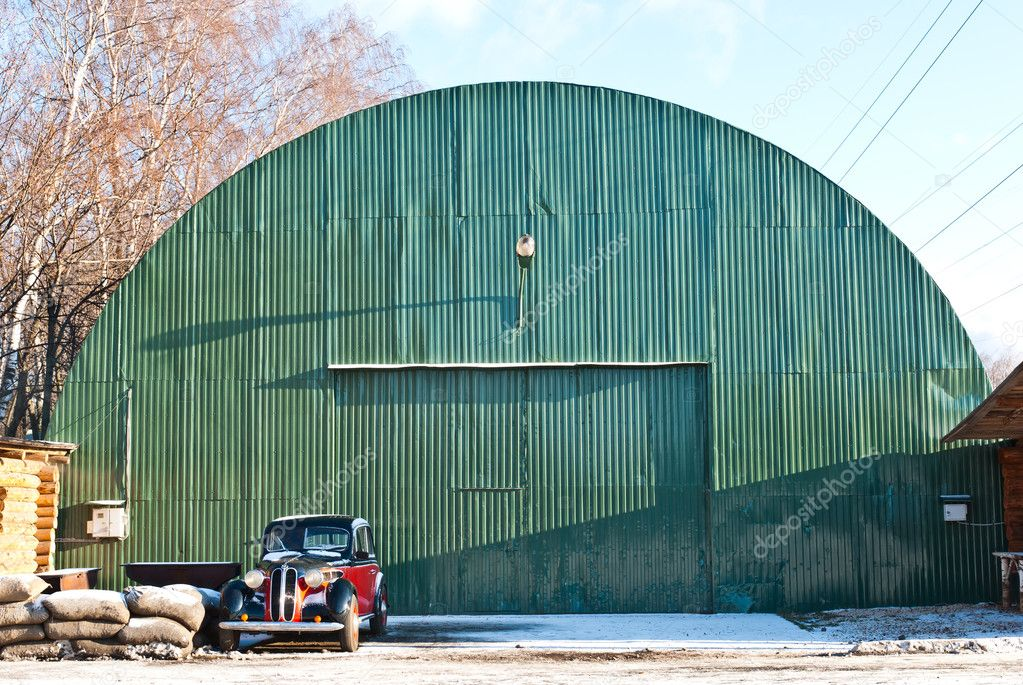 Old green aircraft hanger with classic car park in front, taken on a sunny winter morning — Stock Photo #8196606