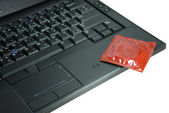 Condom on laptop — Stock Photo