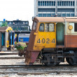 Old diesel train moving away from train station - Stock Photo
