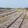 Large railway yard landscape with train on the right - Stock Photo
