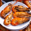 Flame grilled large prawns on white plates - Stock Photo