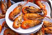 Flame grilled large prawns on white plates — Stock Photo