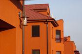 Preciosos apartamentos naranjas con cielo azul - foco de la lámpara — Foto de Stock