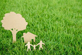 Paper cut of family with house and tree on fresh spring green gr — Stock Photo