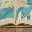 Paper cut of family symbol under tree on old book — Stock Photo