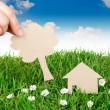 Stock Photo: Hand hold paper cut of House over fresh spring green grass