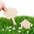 Hand hold paper cut of House over fresh spring green grass — Stock Photo