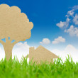 Paper cut of house and tree on fresh spring green grass — Stock Photo #10468976