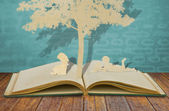 Paper cut of children read a book under tree on old book — Stock Photo