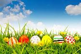 Uova di pasqua con fiore sulla fresca erba verde — Foto Stock