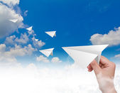Hand throwing a paper plane in the sky — Stock Photo