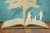 Corte de papel de símbolo de família sob a árvore no livro velho — Foto Stock