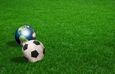 Soccer ball and earth on green grass — Stock Photo