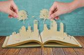 рука держать бумаги вырежьте дерева поверх бумаги вырезать из городов с автомобилем — Стоковое фото