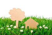Paper cut of house and tree on fresh spring green grass — Stock Photo