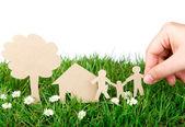 Ręka trzymać cięcia papieru rodziny nad trawa wiosna świeży zielony — Zdjęcie stockowe