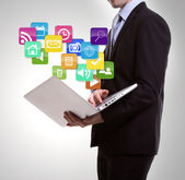 Business man with laptop and colorful application icons — Stock Photo