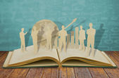 Paper cut of business man on old book — Stock Photo