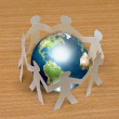 Royalty-Free Stock Photo: Paper cut of  standing in a circle around globe on wooden