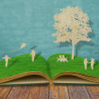 Paper cut of children play on old grass book — Stock Photo