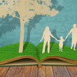 Paper cut of family symbol under tree on old grass book - Stock Photo