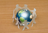 Paper cut of standing in a circle around globe on wooden — Stock Photo