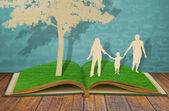 Paper cut of family symbol under tree on old grass book — Foto de Stock