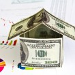 House made from dollars on financial Graphs — Stock Photo #10614458