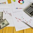 Pen ,calculator and dollars on financial Graphs — Stock Photo #10614551