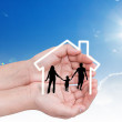 Hand with the silhouettes of the family and house — Stock Photo #10615449