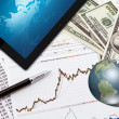 Business graph,touchpad, pen,earth and dollars on table — Stockfoto