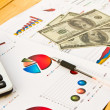 Pen ,calculator and dollars on financial Graphs — Stock Photo #10618044