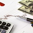 Pen ,calculator and dollars on financial Graphs - Stock Photo