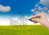 Business hand with pen drawing a house — Stock Photo