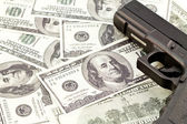 Close up image of pistol and dollar — Stock Photo