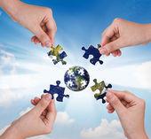 бизнес-концепция с рукой, здание головоломки глобус — Стоковое фото