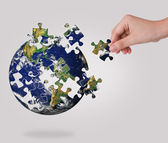 Business concept with a hand building puzzle globe — Stock Photo