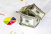 House made from dollars on financial Graphs — Stock Photo
