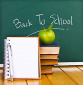 Back to school written on chalkboard with green apple and books — Stock Photo