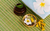 Frangipani flowers and leaves with zen stones on a bamboo mat — Stock Photo