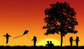 Silhouettes of children read book under tree — Stock Photo