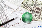 Business graph,touchpad, pen,earth and dollars on table — Stock Photo