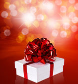 Gift in box with red ribbon and bow — Stock Photo