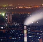Night scene of chimney with smoke in residents area in heavy fog — Stock Photo