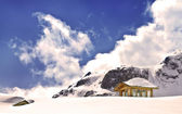Wooden cottage on peak of Yulong Snow Mountain — Stock Photo